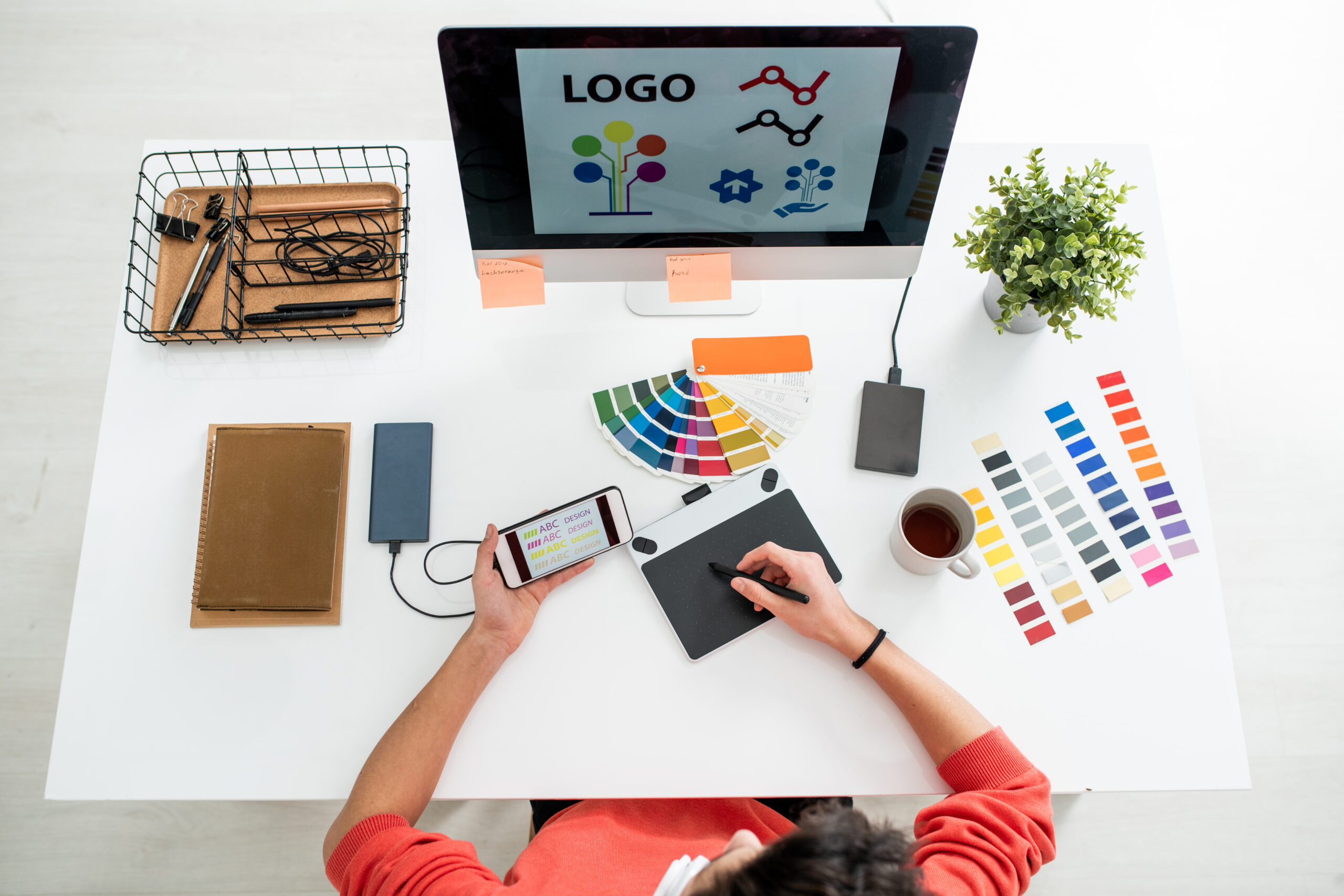 Flat layout of young web designer with stylus and graphics tablet choosing printing type for logo on computer screen