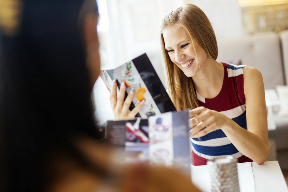Two beautiful women looking at menu in restaurant and smiling