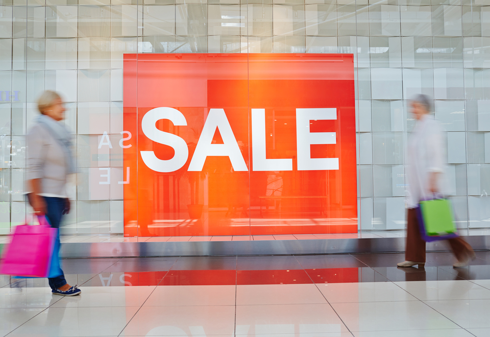 Sale billboard in shopping mall and moving people near by